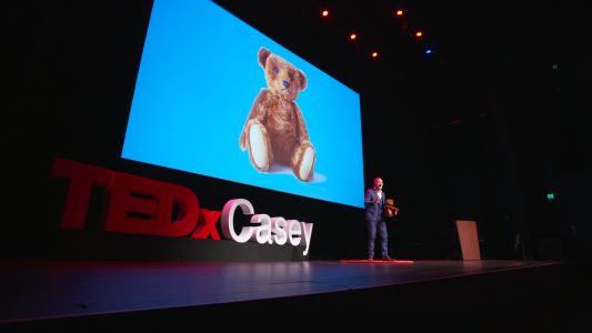 Mark presents at TEDX Casey. Paws & effect: How teddy bears increase value perception